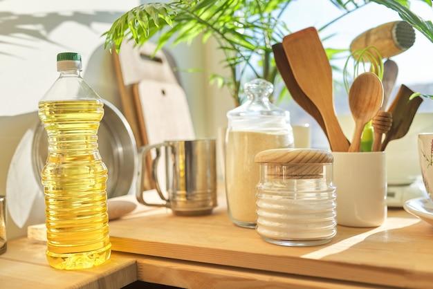 Кухонная утварь, подсолнечное масло и мука на деревянном столе