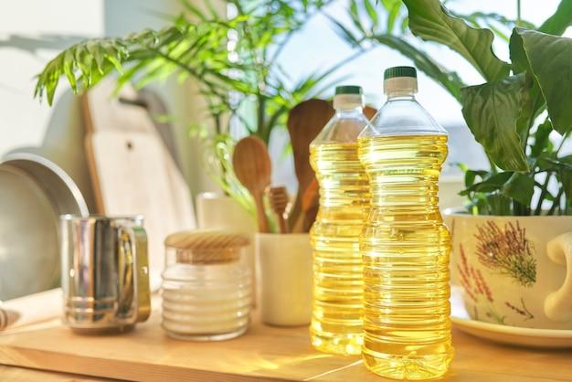 Кухонная утварь, подсолнечное масло на деревянном столе в кладовой, хранение продуктов в домашних условиях