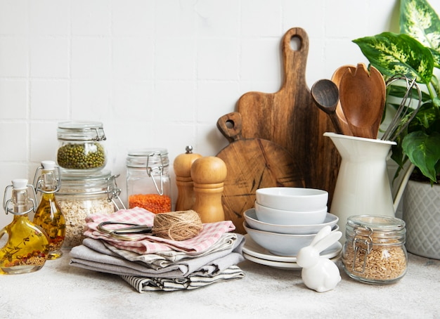 背景の白いタイルの壁に台所用品、道具、食器。明るい色のインテリア、モダンなキッチンスペース。テキスト用の空白スペース、正面図