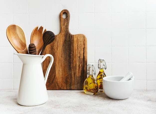 Кухонная утварь, инструменты и посуда на стене белой плитки предпосылки. интерьер, современное кухонное пространство в светлых тонах. пустое место для текста, вид спереди