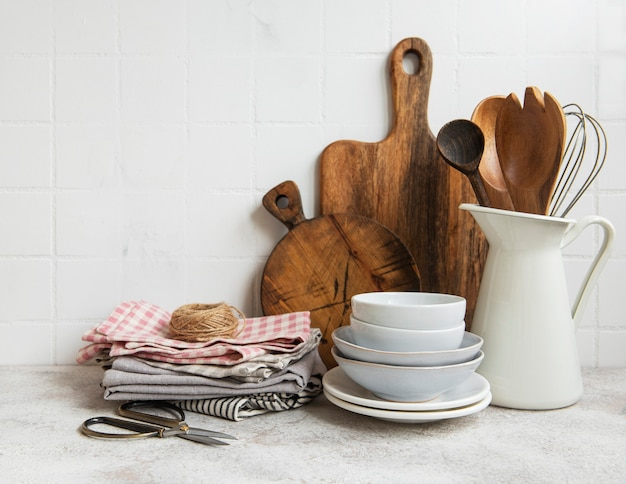 Kitchen utensils tools and dishware on on the background white tile wall