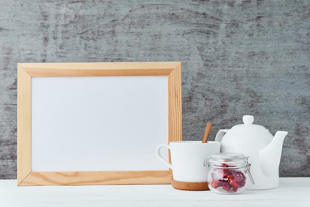 Kitchen utensils with empty white paper, teapot, cup and a honey in glass jar