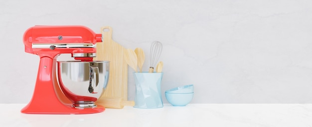 Kitchen utensils with white wall and table and a red kitchen mixer in front