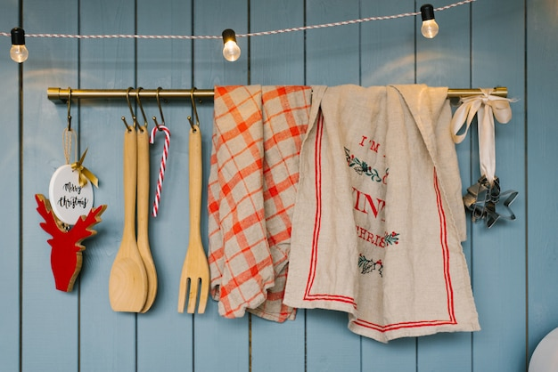 Kitchen utensils: wooden spoons and spatulas, linen towels on the holder in the kitchen in blue tones in scandinavian style, decorated for christmas and new year