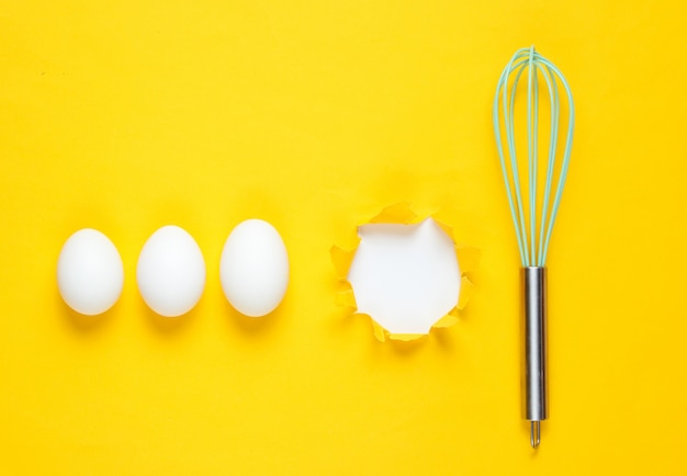 Kitchen whisk, chicken eggs on yellow table. torn hole of yellow paper for copy space. top view