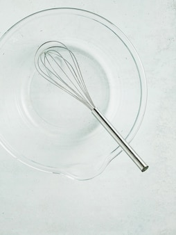 Kitchen whisk in an empty glass bowl on the table.