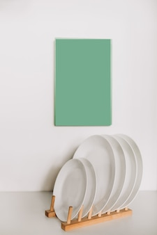 Kitchen white plates on a wooden stand on a background of mint mocap white painted plates in a decorative wooden stand.