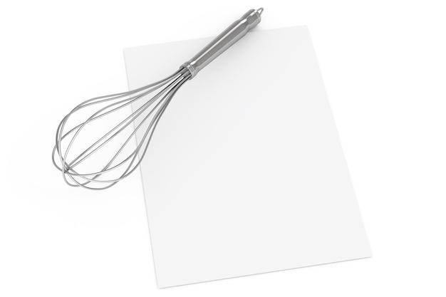 白い背景の上の空白のレシピ紙の上にキッチンワイヤー泡立て器の卵ビーター。 3dレンダリング