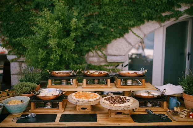 연회를 위해 준비된 음식과 함께 피자를 제공하기위한 프라이팬과 나무 판자가있는 주방