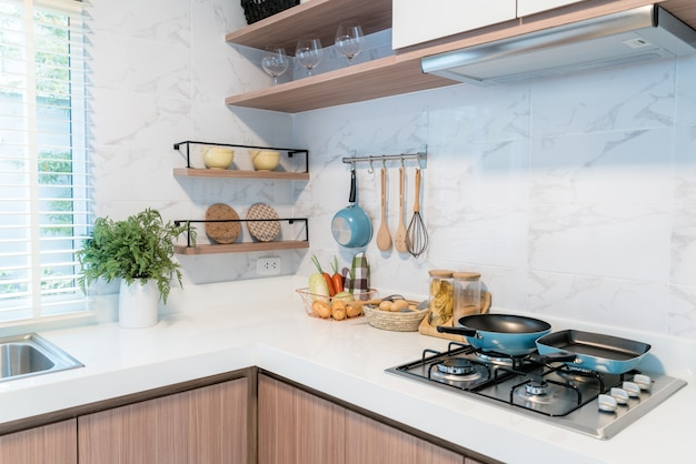 Kitchen wood utensils, chef accessories. hanging copper kitchen with white tiles wall.