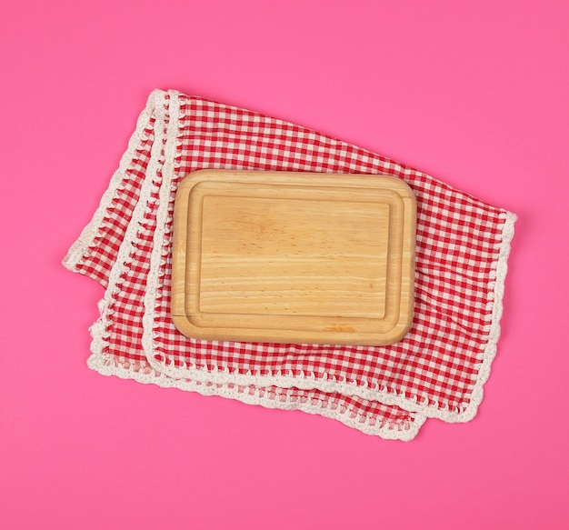 Kitchen wooden cutting board and white red checkered kitchen towel