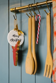 Kitchen wooden spatulas and fork vit on a hook in the kitchen, cooking accessories, and christmas tree toys
