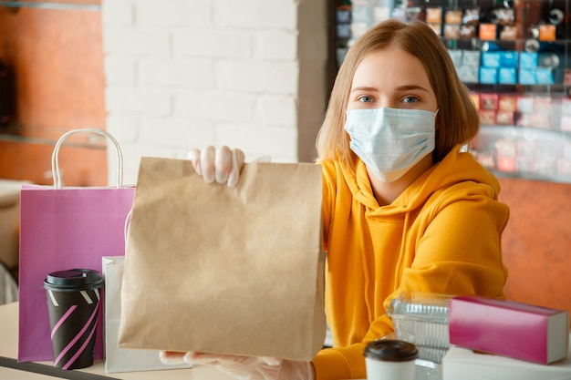 Kitchen worker portrait issues online orders in gloves and mask. takeaway food paper bag. food bag package to go in takeaway canteen. contactless food delivery during lockdown covid 19.
