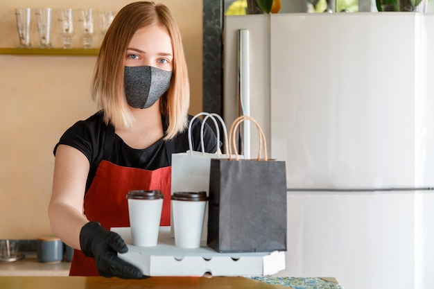 Kitchen worker portrait issues online orders in gloves and mask. takeaway food paper bag mock up. food bag, pizza, drink package to go in takeaway canteen. contactless food delivery lockdown covid 19.