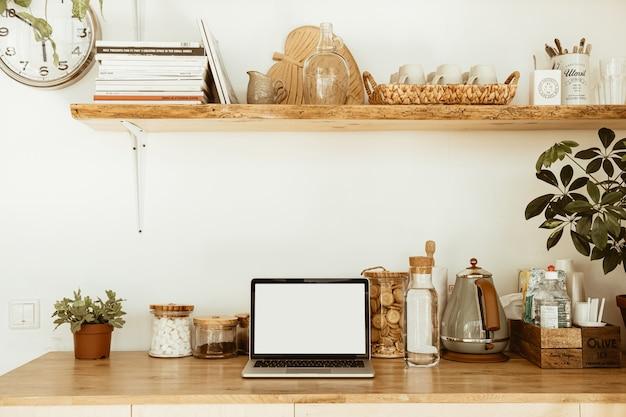 空白のコピースペースのあるキッチンワークスペースは、ノートパソコンの画面をモックアップします。木製の台所用品を備えたモダンでスタイリッシュなキッチンのインテリアデザイン。