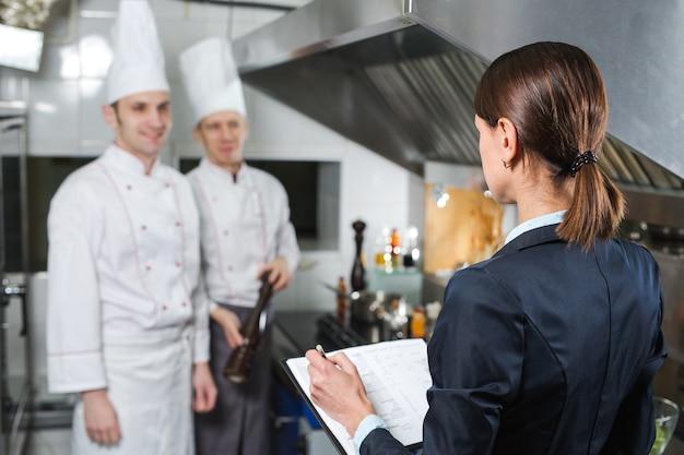 業務用kitchen房のキッチンスタッフに説明するレストランマネージャー