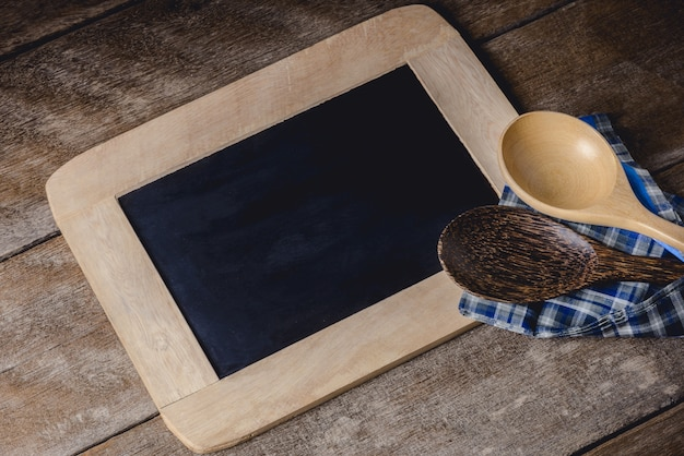Kitchenware on a blackboard with a blue checkered napkin