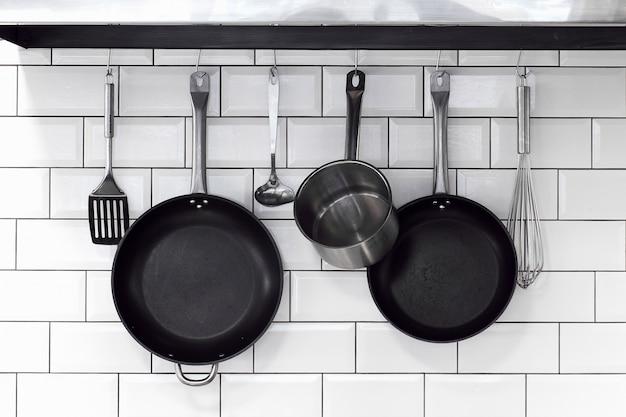 Kitchenware hanging on a white brick wall