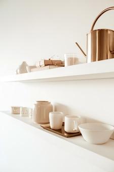 Kitchenware utensils on shelf on white. ceramic mugs, cups, teapot, tray.