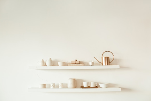 Kitchenware utensils on shelf on white surface