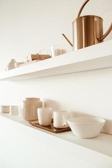 Kitchenware utensils on shelf on white