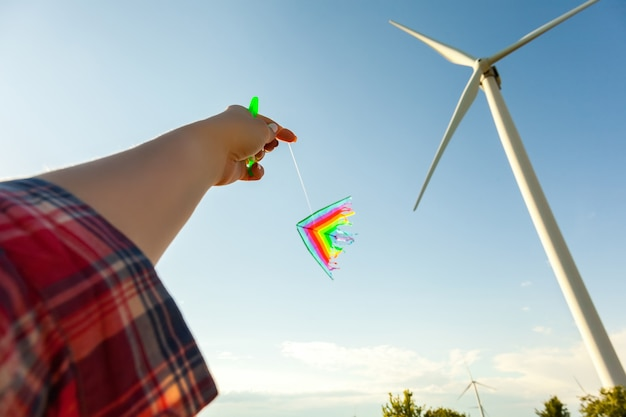 Kite flying in a beautiful sky with sun and white wind turbines against the blue sky