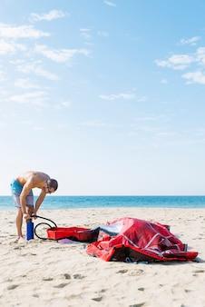 Кайтсерфер надувает кайт на пляже.