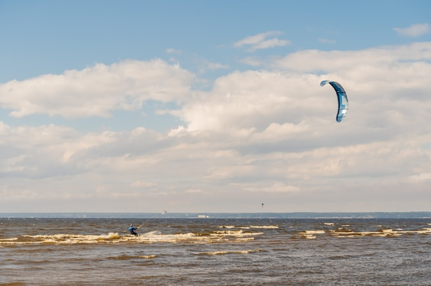 The kitesurfer is riding on the waves of the bay