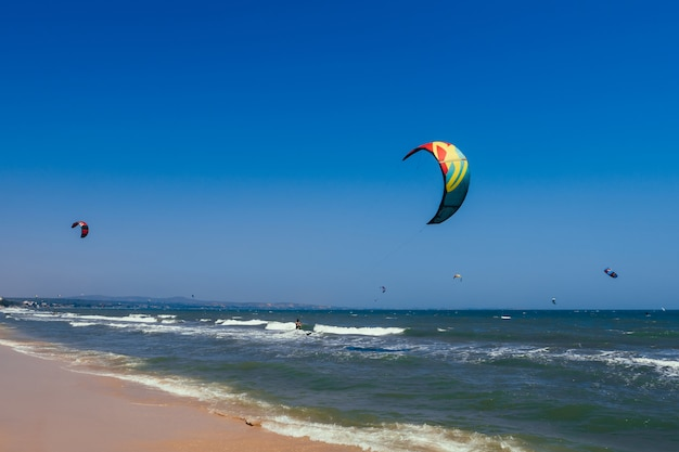 Kitesurfing on the waves of the sea on the beach on a sunny day