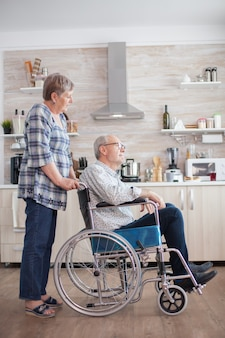 In the kithcen old woman is looking at handicapped husband who is in wheelchair. disabled senior man sitting in wheelchair in kitchen looking through window. living with handicapped person. wife helpi