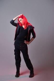 キッチュなスタイル、未来のファッション。混合スタイル。灰色の背景に暗い珍しい服を着た明るい緋色の髪の若い女性