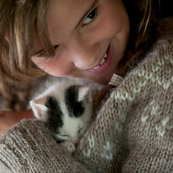 Kitten cuddled by girl