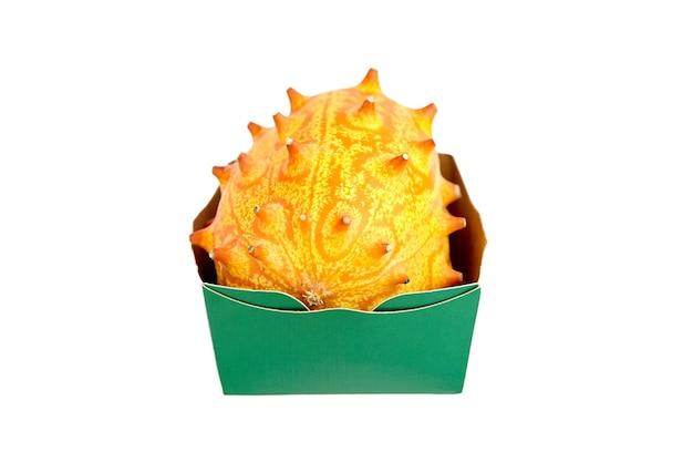 Плоды дыни кивано или рогатая дыня в лотке для бумаги, изолированные на белом фоне