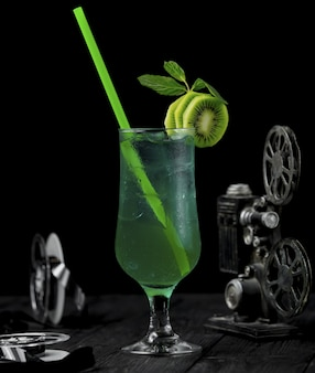 Kiwi alcohol cocktail with fruit slices and green pipe.