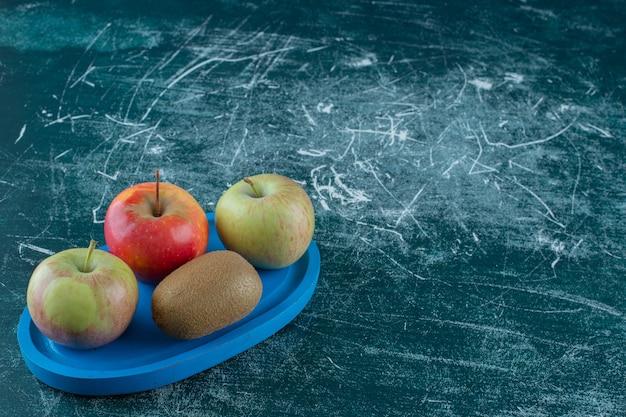 Киви и яблоки на деревянной тарелке, на мраморном столе.