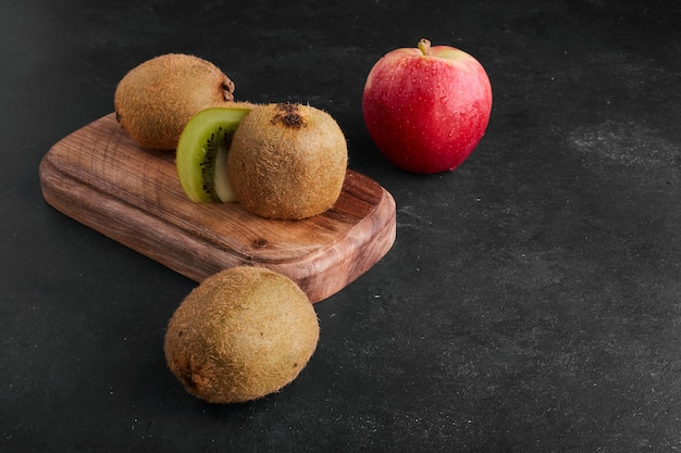 Kiwi and apples on wooden board.