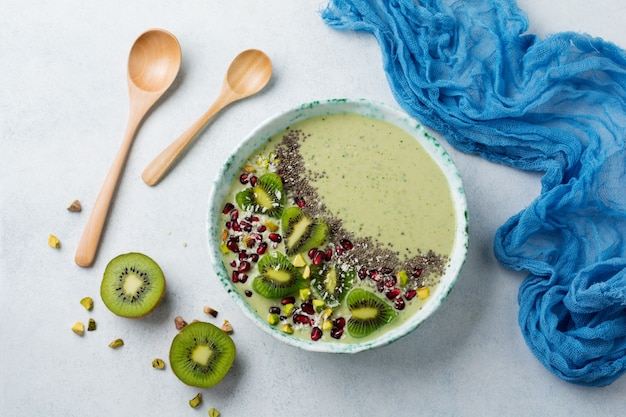 Kiwi banana smoothies bowl with oatmeal, pistachio nuts, pomegranate seeds and chia on light gray stone background