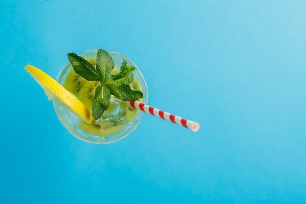 Коктейль из киви, украшенный лимоном и мятой, в стакане на салфетке на синей поверхности, вид сверху