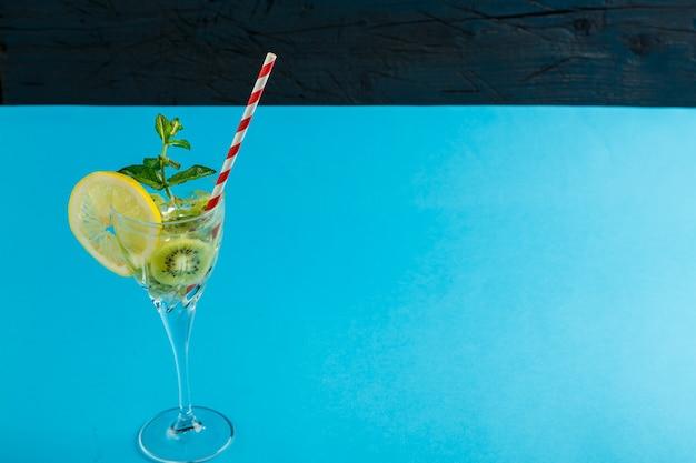 Коктейль из киви, декорированный лимоном и мятой, в стакане на салфетке на синей поверхности