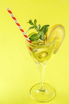 Коктейль из киви, украшенный лимоном и мятой в стакане на салфетке на желтой поверхности