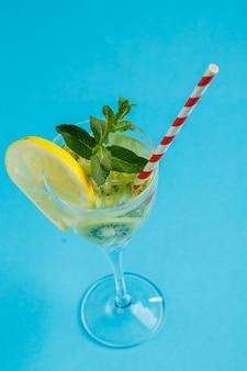 Коктейль из киви, украшенный лимоном и мятой, в стакане на салфетке на синей поверхности