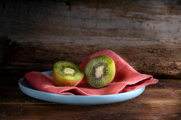 Kiwi cut in two halfs in a wooden table