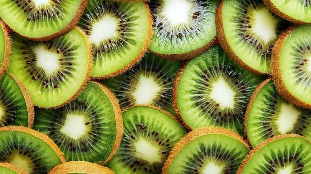 キウイフルーツは、背景としてフルスクリーンでスライスにカットされています。