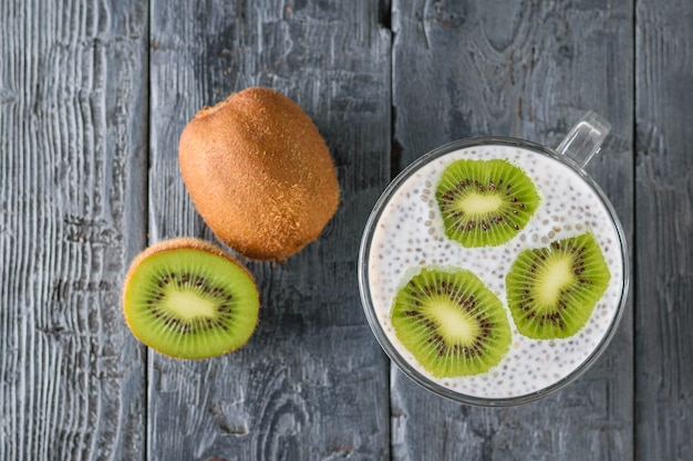 Kiwi fruit and a mug of black chia seed pudding on a black wooden table. the view from the top. flat lay.