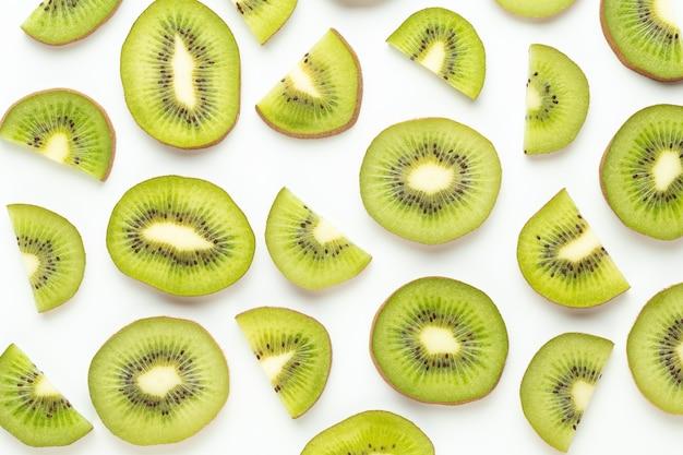 キウイフルーツスライスマクロ。白い表面に分離された熟したキウイフルーツ。フラットレイ。