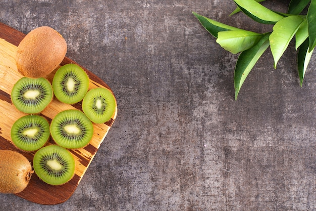 Kiwi fruit on a wooden board top view on black stone surface
