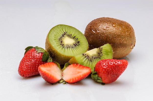 白い背景で隔離のキウイフルーツとイチゴ