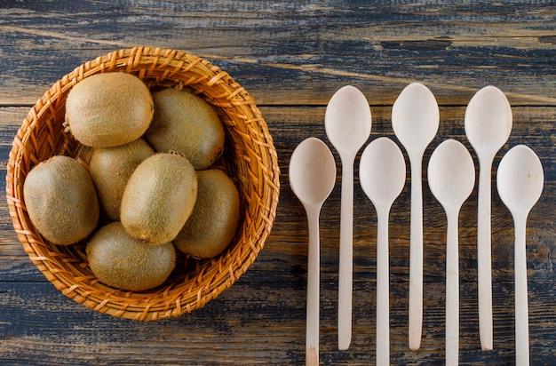 フラット木製の背景に籐のかごでスプーンでキウイフルーツを置きます。