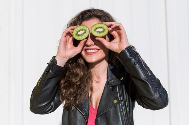 Kiwi. healthy fruit funny woman holding kiwi fruit for her eyes. lifestyle. white.