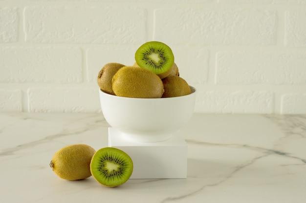 大理石のキッチンテーブルの表彰台にある白いボウルに入れられたキウイ。フレッシュでジューシーなトロピカルフルーツ。